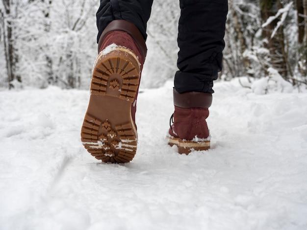 Ein mann in stiefeln geht durch den winterwald. ansicht von unten auf schuhe, selektiver fokus. konzept von wanderungen, spaziergängen und winterferien