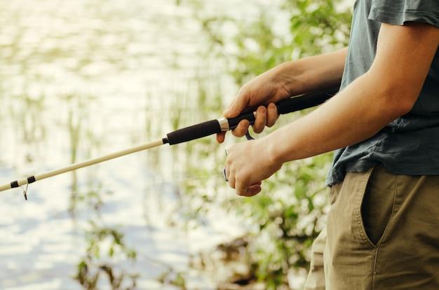 Ein mann in t-shirt und dunkler hose fischt auf dem see mit einer weißen angelrute gegen büsche und gras