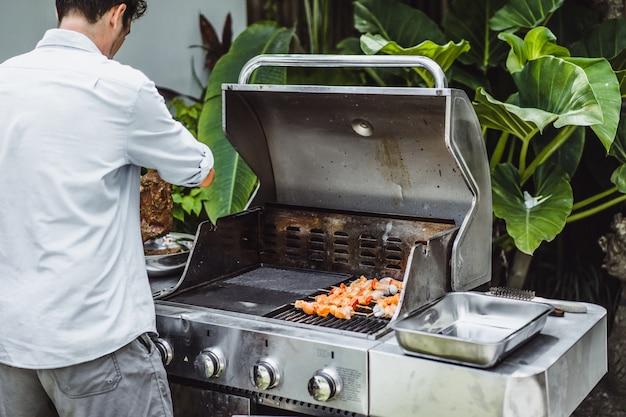 Ein mann in tätowierungen macht barbecue grill fleisch im freien.