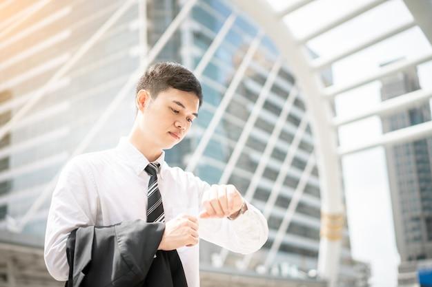 Ein mann in weißem hemd und krawatte hält schwarzen anzug.