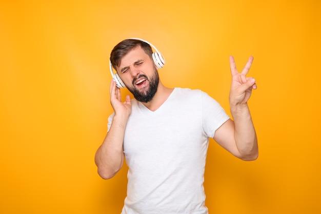 Ein mann in weißen kopfhörern mit bart, hört musik und zeigt die siegesgeste.