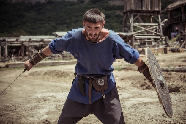 Ein mann in wikinger-tracht hält ein schwert und einen schild