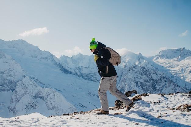 Ein mann in winterkleidung steigt auf den berg.