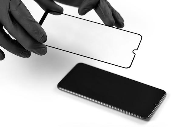 Ein mann installiert ein schutzglas auf dem bildschirm eines smartphones.
