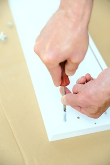 Ein mann installiert gelenkverbindungsschrauben in der möbelplatte.