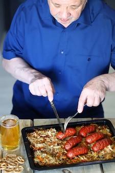 Ein mann isst würstchen mit sauerkraut und bier.