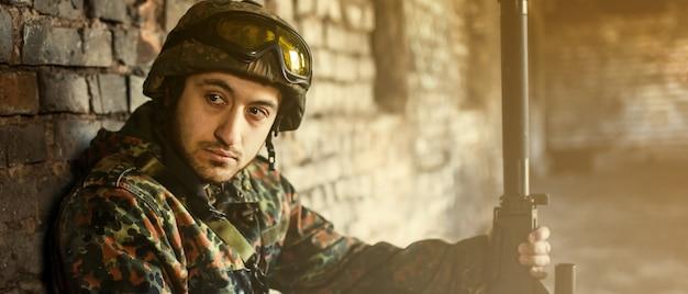 Ein mann ist ein militärsoldat in helm und tarnkleidung. nachdenklicher soldat, der sich von einer militäroperation ausruht