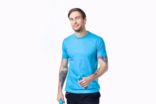 Ein mann ist mit hanteln in den händen auf hellem hintergrund und einem tattoo-modell in fitness beschäftigt