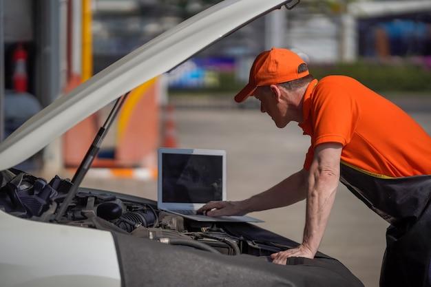 Ein mann ist motorenmechaniker und überprüft den motor mit einem laptop