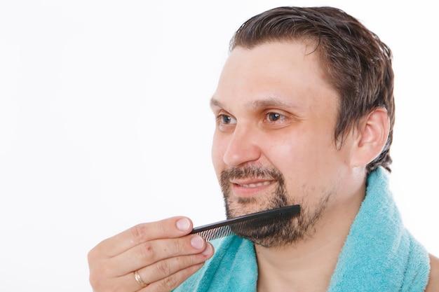 Ein mann kämmt seine stoppeln. der typ bürstet sich den bart. blaues handtuch um ihren hals. isoliert auf einem weißen hintergrund.