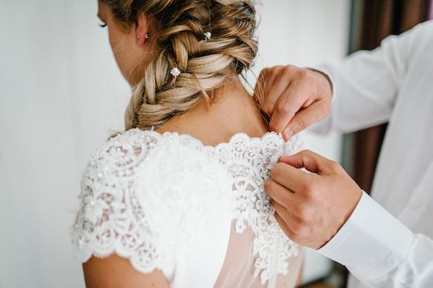 Ein mann knöpft das korsett des kleides zu. braut im weißen hochzeitskleid mit spitze, die im raum steht. rückansicht.