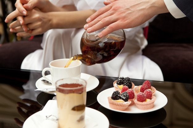Ein mann kümmert sich um eine frau: gießt ihren grünen tee ein. auf dem tisch stehen desserts: tiramisu und gebäck mit frischen beeren. ohne gesichter im rahmen der hand. nahansicht