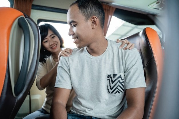 Ein mann lächelt, als eine frau vor dem hintergrund eines busfensters im bus seinen rücken packt