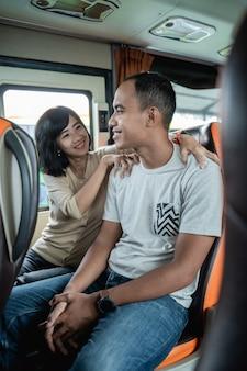 Ein mann lächelt, als eine frau vor dem hintergrund eines busfensters seinen rücken massiert, während er in einem bus sitzt
