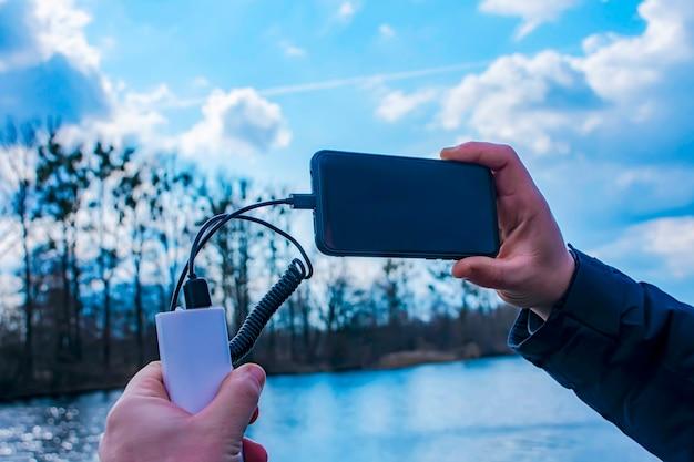 Ein mann lädt ein smartphone mit einer powerbank auf. das handy in der hand wird mit einem tragbaren ladegerät vor der kulisse des sees aufgeladen.