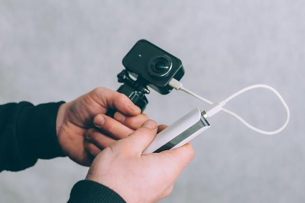 Ein mann lädt eine action-kamera mit einem tragbaren ladegerät auf.
