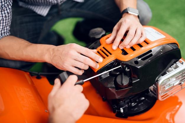 Ein mann lässt im laden einen rasenmähermotor an.