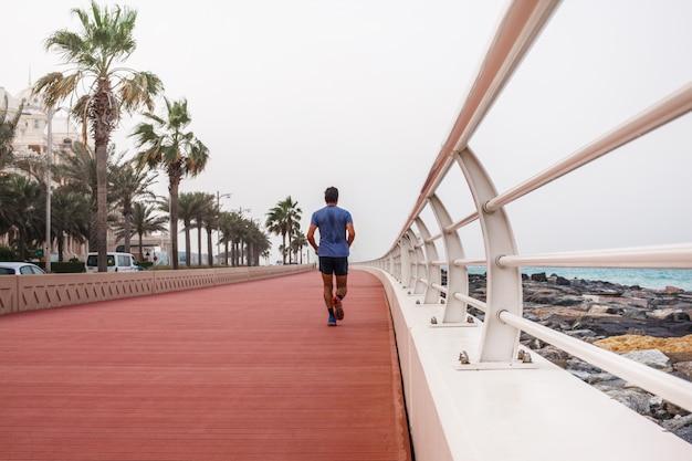 Ein mann läuft entlang einer schönen promenade mit einem weißen zaun.