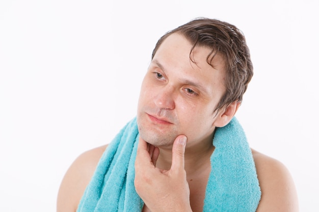 Ein mann legt aftershave auf sein gesicht. der mann streichelt sein gesicht. morgenbehandlungen im badezimmer. speicherplatz kopieren