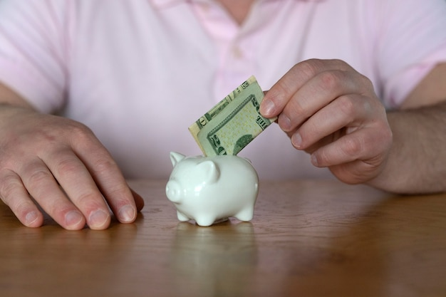 Ein mann legt eine dollarbanknote zum sparen in ein sparschwein