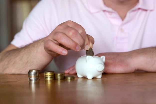 Ein mann legt eine münze in ein sparschwein, um zu sparen