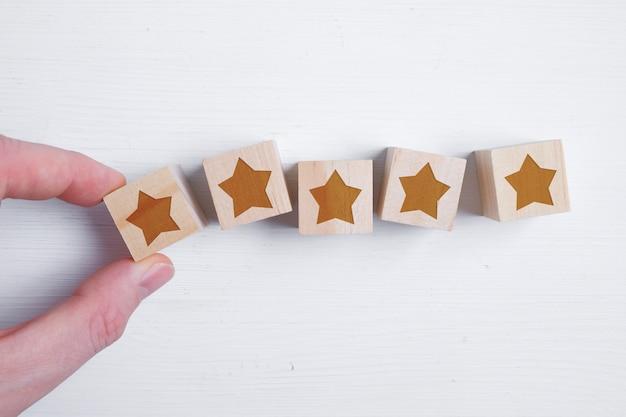 Ein mann legt fünf sterne auf hölzerne würfel, wobei seine hand die beste bewertung zeigt. bestes ergebnis. flach liegen.