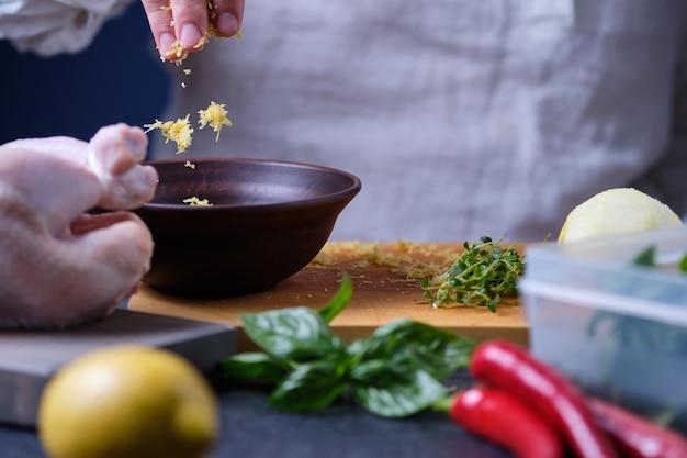 Ein mann legt zitronenschale in einen teller der prozess des kochens von hühnchen mit gewürzen und zitrone im ofen