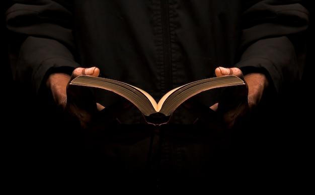Ein mann liest ein buch in der dunkelheit