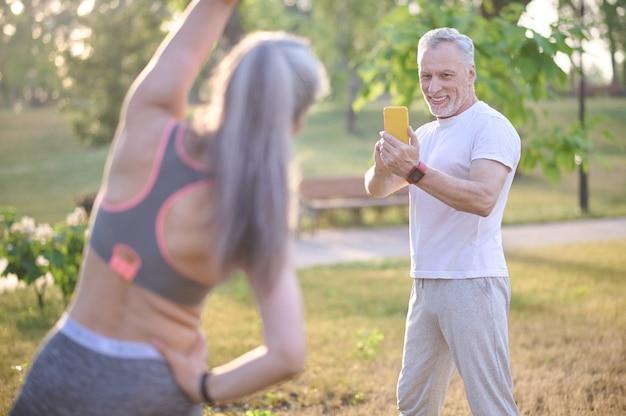 Ein mann macht ein foto von seiner frau, während sie trainiert