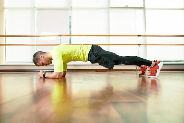 Ein mann macht ein übungsbrett in der halle auf dem boden gegenüber dem fenster. sportlicher lebensstil, bewegungsleben.