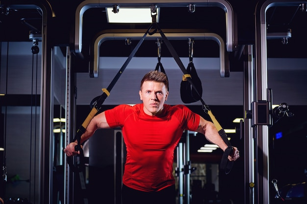 Ein mann macht übungen am simulator in der turnhalle