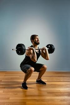 Ein mann macht übungen mit einer langhantel auf grauem hintergrund. der athletische körper eines jungen mannes in muskelverspannung macht einen annäherungsversuch mit einer langhantel. platz kopieren.