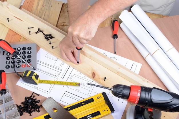 Ein mann machte ein möbelstück mit verschiedenen tischlerwerkzeugen