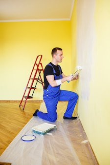 Ein mann malt die wand im haus mit rolle und farbe. renovierung der zimmer im haus.