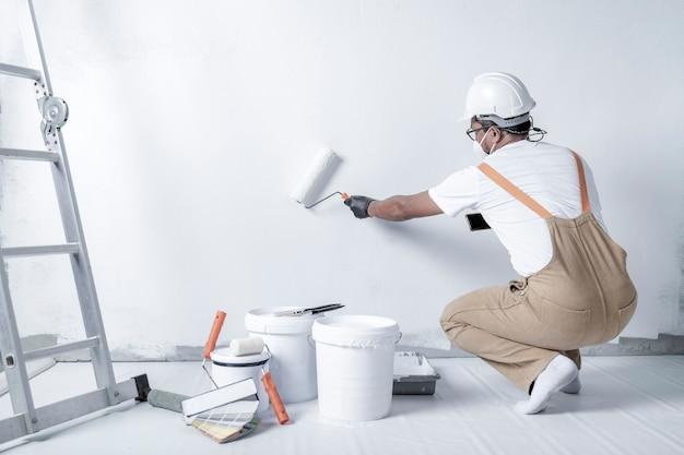 Ein mann malt eine weiße wand mit einer rolle reparatur des innenraums