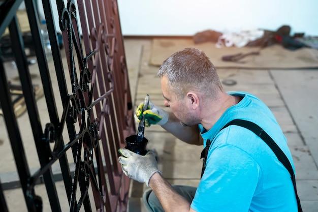 Ein mann malt einen handgefertigten schmiedeeisernen zaun.