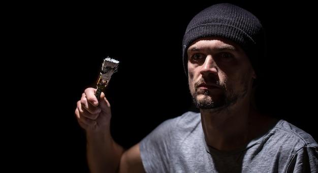 Ein mann malt einen pinsel mit weißer farbe auf einem schwarzen hintergrund. mann im industriellen konzept. es gibt einen platz für text, objekt hautnah