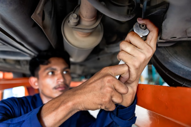 Ein mann mechaniker blick auf motorlicht. service-auto in der garage ist papier checkliste auto. service-auto, reparatur, wartungskonzept. techniker macht die checkliste für reparaturmaschine ein auto in der garage.