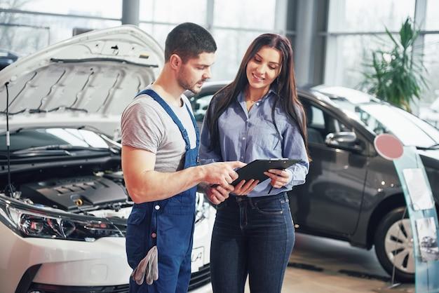 Ein mann mechaniker und frau kunde diskutieren reparaturen an ihrem fahrzeug durchgeführt
