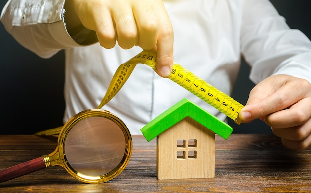 Ein mann misst und bewertet ein haus fair value von immobilien und wohnungen immobilienbewertung
