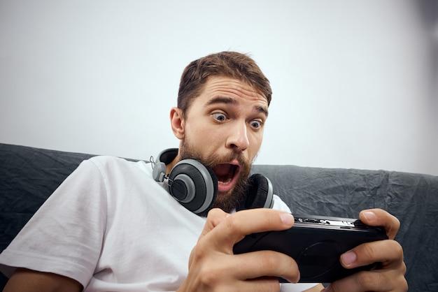 Ein mann mit 3d-brille spielt ein computerspiel auf konsolen mit joysticks in kopfhörern auf einem sofa zu hause