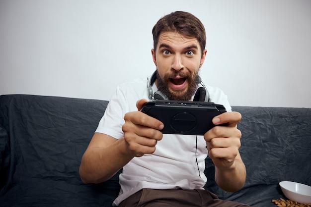 Ein mann mit 3d-brille spielt zu hause ein computerspiel auf konsolen mit joysticks in kopfhörern auf einem sofa