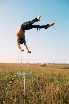 Ein mann mit athletischem körperbau führt bei sonnenuntergang komplexe gymnastikübungen auf einem feld durch