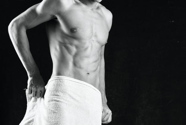 Ein mann mit aufgepumptem körper bedeckt sich mit einem handtuch studio fitness. foto in hoher qualität
