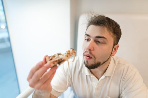 Ein mann mit bart, der eine pizza kaut. der student isst ein leckeres stück pizza und sieht ihn aufmerksam an