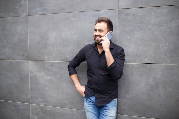 Ein mann mit bart geht und spricht telefonisch