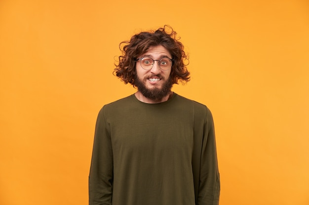 Ein mann mit bart in brille und lockigem dunklem haar, der nach vorne schaut, beißt sich auf die lippe, verwirrt