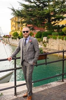 Ein mann mit bart in einem strengen grauen dreiteiler mit krawatte in der altstadt von sirmione, ein stylischer mann in einem grauen anzug in italien.