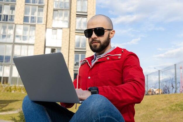 Ein mann mit bart in roter jacke und jeans sitzt auf einer bank und arbeitet an einem computer. das konzept der freiberuflichen arbeit