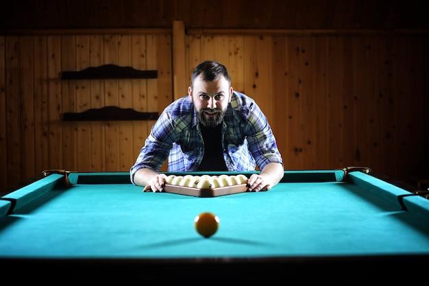 Ein mann mit bart spielt ein großes billard. party im 12-fuß-pool. billard im vereinsspiel für männer. ein mann mit einem queue durchbricht die pyramide.